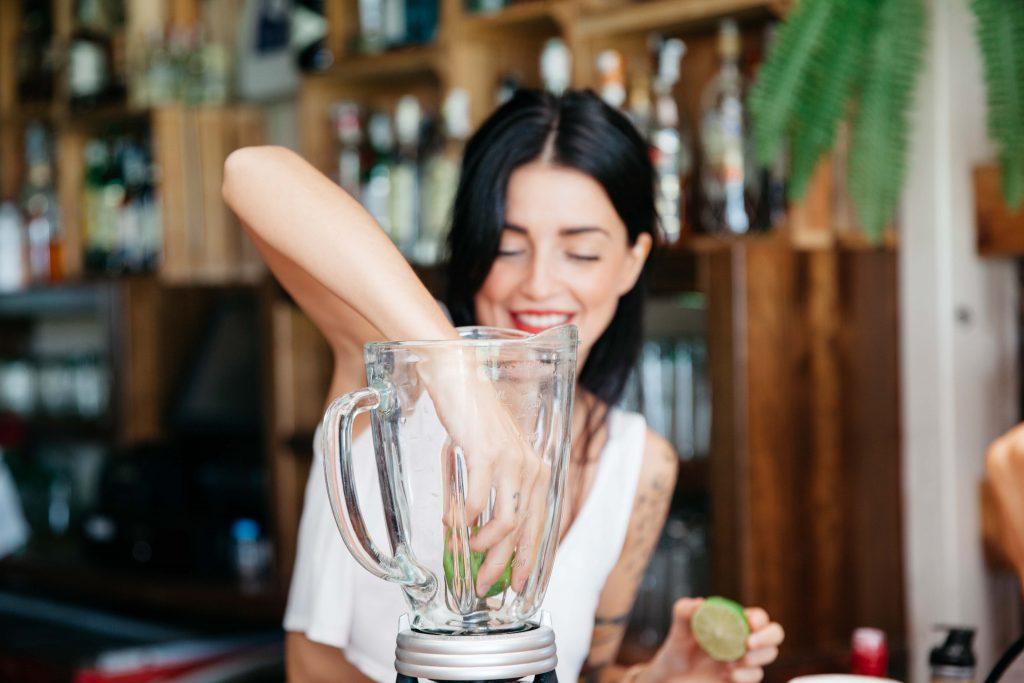 Woman making low FODMAP smoothie in blender