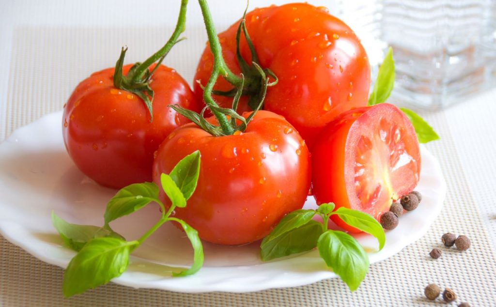 Low FODMAP fresh and juicy tomatoes with basil leaves