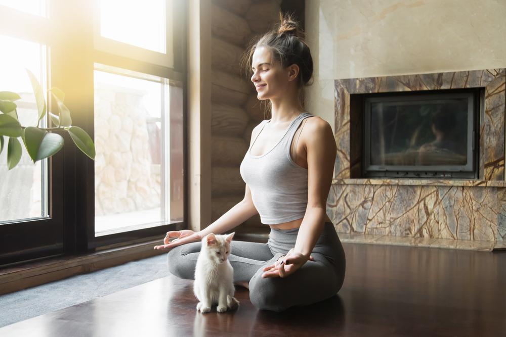 Girl Practising Yoga for IBS with Kitten